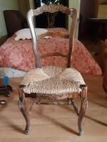 Wooden chair with designs engraved throughout along with woven seating