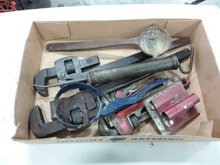 assortment of pipe wrenches and hand tools