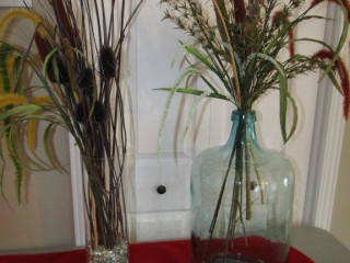 Pair of large glass bottles with artifical flowers