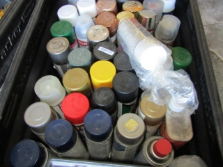 Tub of spray paint partial and full cans
