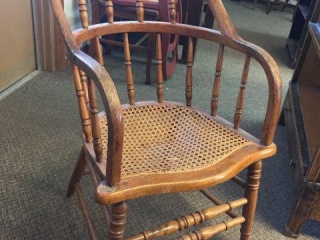 Open arm side chair with caned seat. Damaged