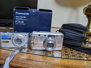 Panasonic FX3 and a Canon Z180U Sure shot. Untested. with cords and a carry bag for the cannon