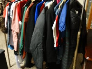 Clothes wrack with misc  winter coats of all sizes and other misc  clothes