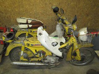 Two Honda passport 70 motorcycles in pieces