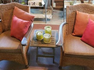 Pair of Rattan Cushioned Patio Chairs  Seat  22 in w Throw Pillows and Wood Accent Fold Up Table  18 x 18 x 18 in  tall w Candle Set