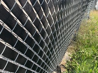 Two rolls of vinyl webbing 100 yards each dress up your chain link fence as pictured