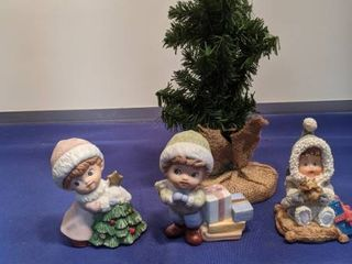 three figurines and a little Christmas tree