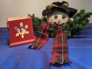 snowman sitting on fir branch and snow flake candle holder
