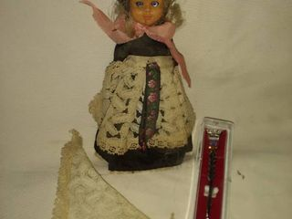 small doll from Germany with lace apron and shawl and souvenir spoon