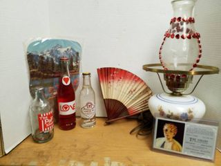 3 soda bottles  2 fans  lamp and a postcard