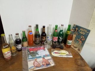 12 soda bottles  Mutt and Jeff comic book  globe glass mug  car bank and 2 advertisements