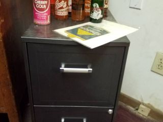 12 soda bottles  1 soda can  advertisement and 2 drawer filing cabinet