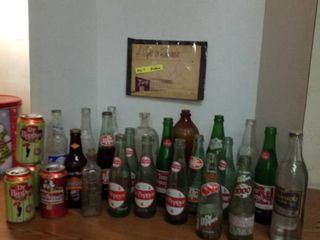 18 soda pop bottles  4 Dr Pepper cans  medicine bottles and an advertisement