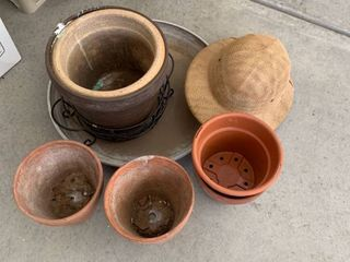 Various pots and holders with a hat