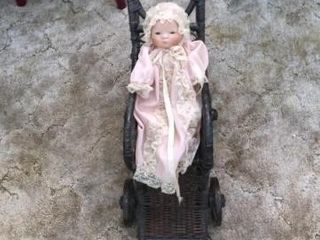 Porcelain doll with vintage wicker stroller and