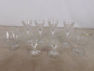 8 assorted glassware including 4 matching glasses  2 deep wine glasses and 2 candle holders