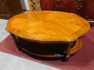 Wooden oval coffee table with cane under shelf 43 in W X 30 in l X 16 1 2 H
