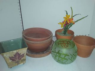 assorted plastic flower pot saucers with two clay pots and various potting items