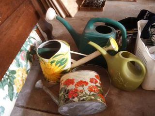 two handpainted and two plastic watering cans