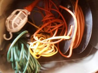tote of outdoor extension cords and reel with drop light