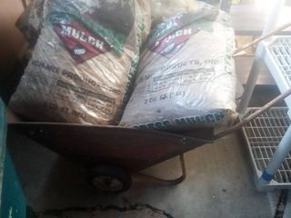 old metal wheelbarrow with 2 bags of mulch
