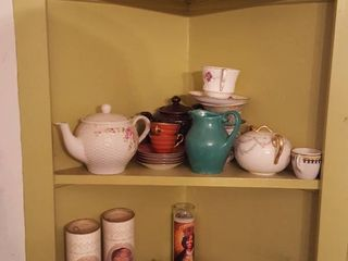 Contents of three shelves  teapot  brass  candles  clocks and more