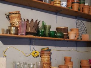 Contents of three shelves  terracotta pots  baskets and vases