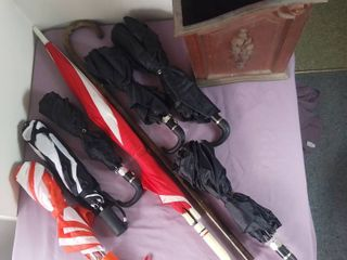 lot of 9 Items   4 Matching Black Umbrellas   2 White And Red Umbrellas   1 Black And White Umbrellas   1 Wooden Kane   1 Wooden looking Plastic Storage Box