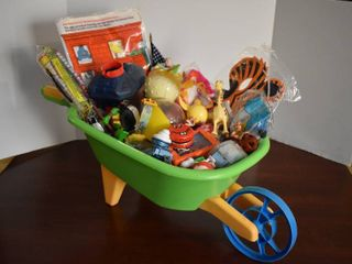 large lot of Assorted Small Toys in Children s Green Wheelbarrow