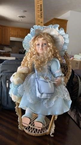 PORCElAIN DOll SITTING ON A CHAIR