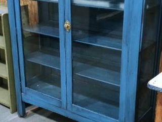 Wooden and glass blue 4 shelf rolling display cabinet 55 x 47 x 15 in one of the casters is broken