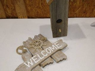 Wooden bird house with wooden and white welcome sign