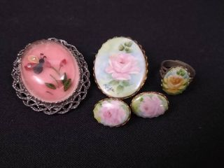 2 decorative shirt pins  one pair of earrings and on costume jewelry ring