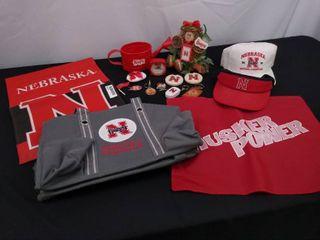 Assorted Nebraska Husker s merchandise including a bag  2 flags  2 hats and a garden decor