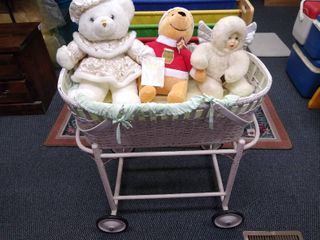Rolling wicker bassinet with 3 teddy bears  2000 limited edition Keepsake bear  Christmas pooh bear and a Green trading angel doll  29 1 2 in H X 30 in W X 17 in D