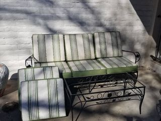 Wrought iron settee  cushions and table  missing glass