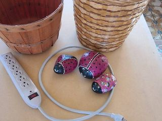 Three painted rocks  power strip  two baskets