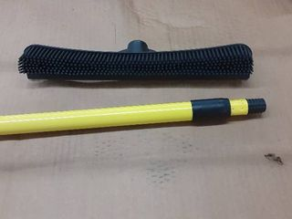 This uniquely designed rubber broom sweeps  scrubs  squeegees and washes out easily  Bristles are electrostatic  Features a telescopic handle for