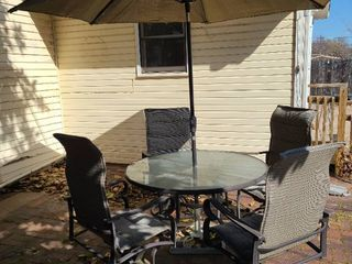 Glass top patio table 48  diameter with 4 swivel chairs  umbrella and stand