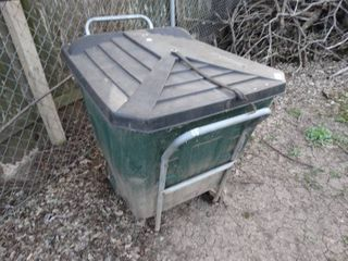 Green Garbage Can on Wheels with Sticks