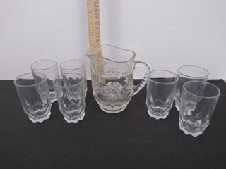 7 small cups and a glass pitcher