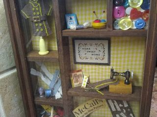 Small shadow box with sewing trinkets