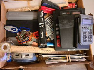 Assorted office supplies including calculators and staplers