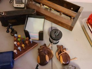 Assorted items including pencil sharpener  post it notes  vintage camera  castanets  etc