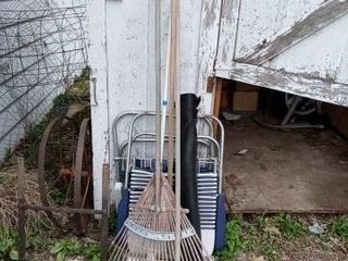 TWO AlUMINUM CHAIRS  A RAKE THREE BROOMS AND